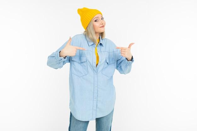 Loira em uma camisa jeans elegante e uma jaqueta amarela sobre fundo branco.