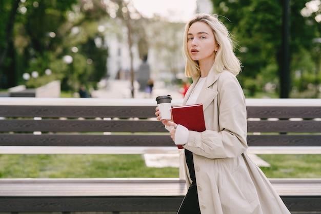 Loira em uma cidade de verão com uma xícara de café