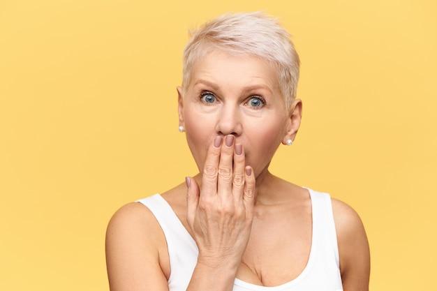 Loira emocional mulher de meia-idade arregalando os olhos e cobrindo a boca com a mão, tentando não contar informações intrigantes ou segredos, tendo surpreendido expressão facial atônita