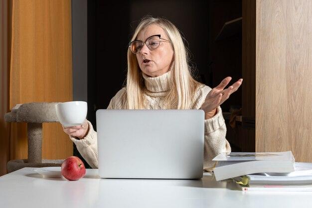 Loira empresária de meia-idade sentada na mesa, bebendo chá e trabalhando com o laptop do escritório em casa