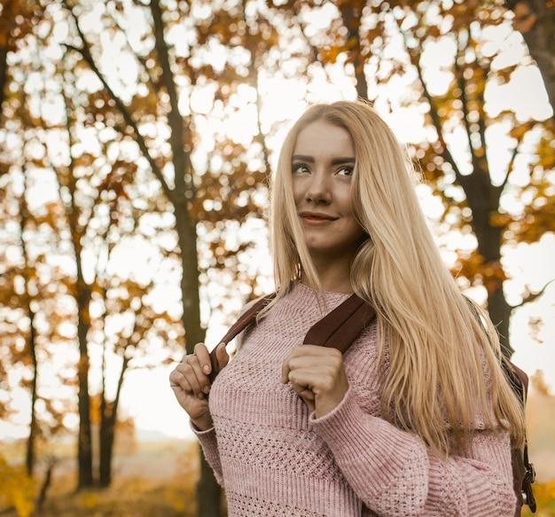 Loira encantadora andando com mochila pela floresta de outono
