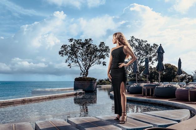 Loira encantadora em um vestido preto de noite posando perto da piscina infinita
