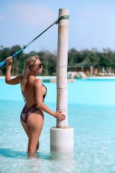 Loira encantadora posando em uma rede perto da piscina