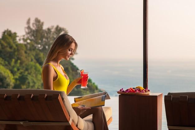 Loira encantadora relaxa em uma espreguiçadeira perto da piscina infinita e bebe um smoothie de melancia