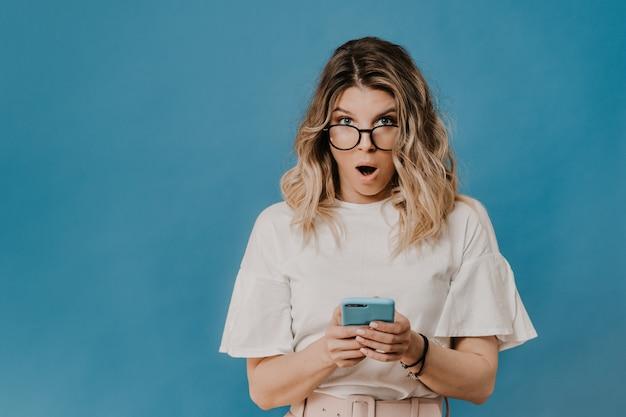 Loira encaracolada de óculos, vestindo uma blusa branca e calça rosa, surpresa e chocada com os olhos bem abertos fica com um telefone nas mãos, sobre um fundo azul com um espaço de cópia. notícias incríveis.