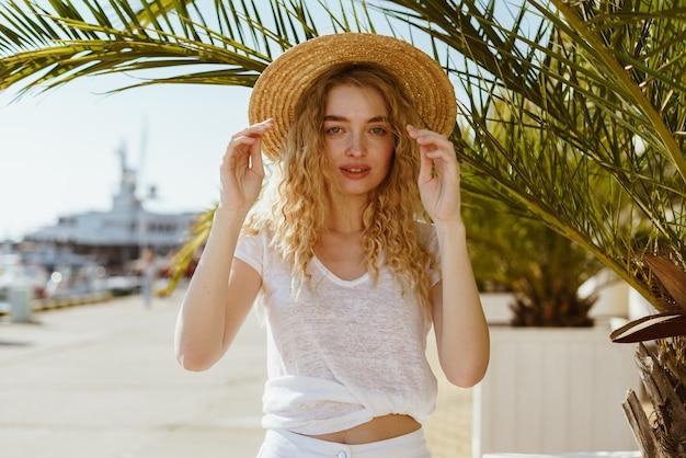 Loira encaracolada segura um chapéu nas mãos e olha cautelosamente à sua frente em um fundo de palma
