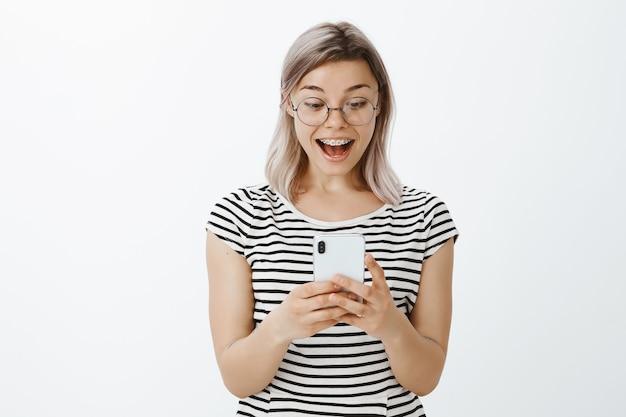 Loira espantada posando no estúdio com seu telefone