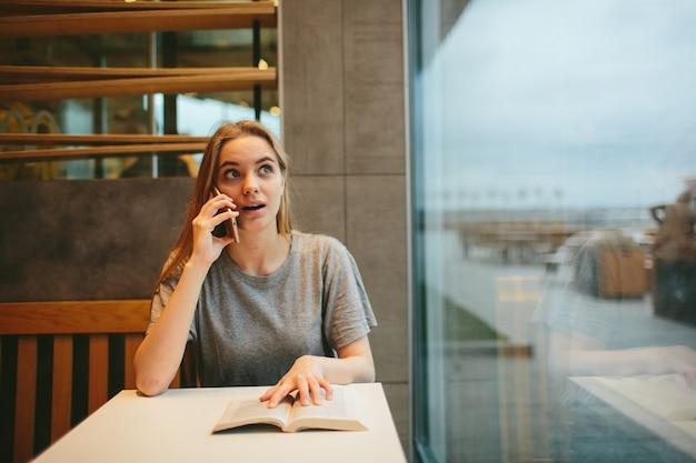 Loira está lendo um livro e falando ao telefone em uma lanchonete ou restaurante.