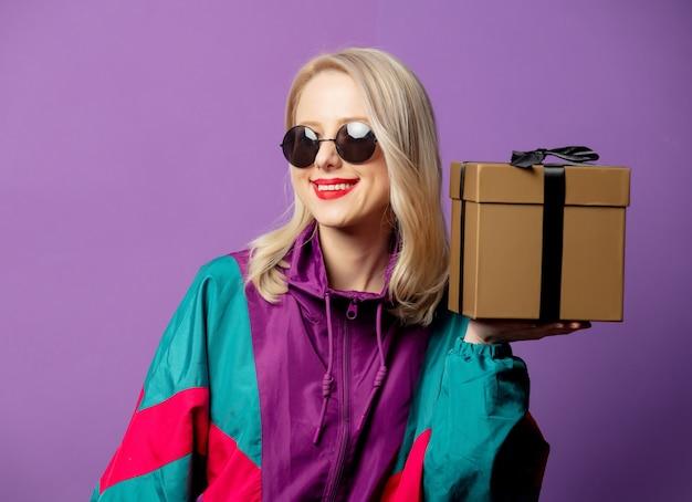 Loira estilosa com blusão dos anos 80 e óculos de sol redondos com caixa de presente na parede roxa