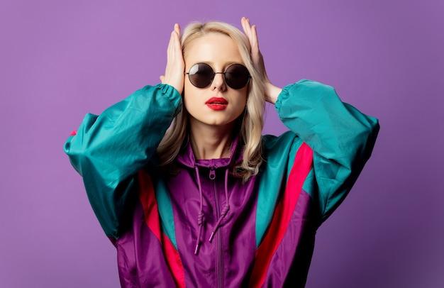 Loira estilosa com blusão dos anos 80 e óculos de sol redondos na parede roxa