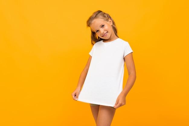 Loira europeia em uma camiseta branca em uma parede amarela