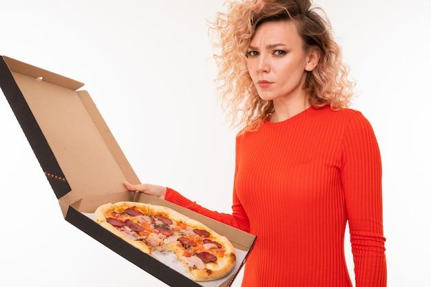 Loira européia encaracolada em um vestido vermelho segura uma caixa de pizza na parede branca do estúdio