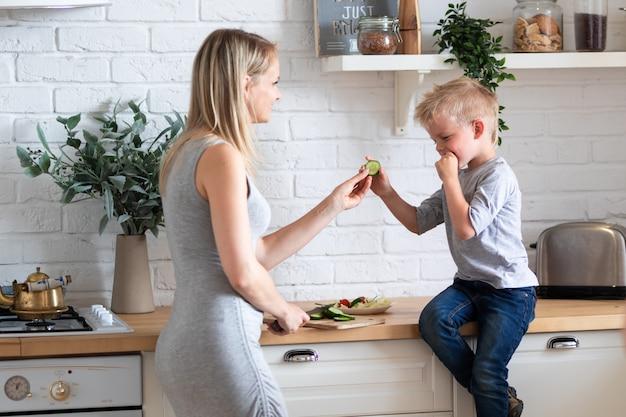 Loira família mãe e filho a comer alimentos saudáveis na cozinha em casa, salada verde em placas