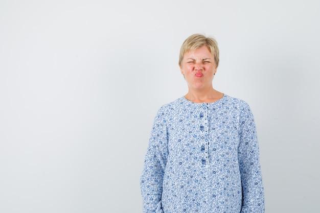 Loira fazendo beicinho enquanto piscava os olhos em uma blusa estampada e parecia engraçada. vista frontal. espaço para texto
