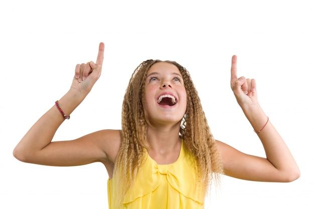 Loira feliz com cabelos cacheados, menina adolescente, apontando o dedo indicador para cima