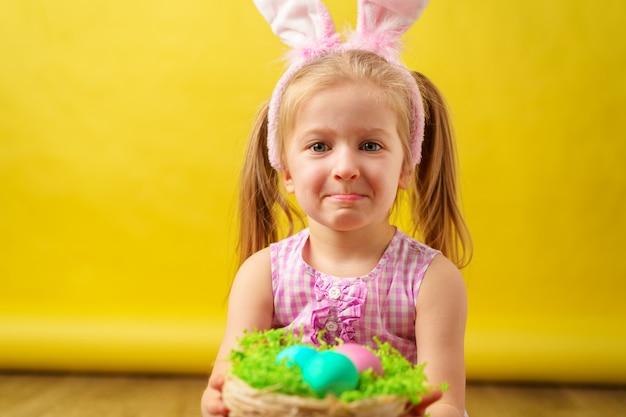 Loira feliz com orelhas de coelho e cesta de ovos de páscoa