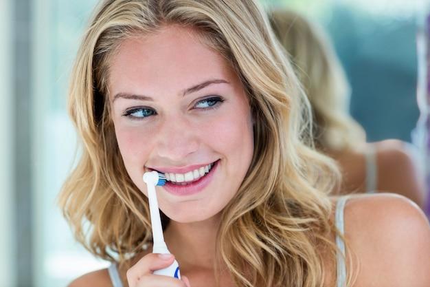 Loira feliz escovando os dentes no banheiro em casa
