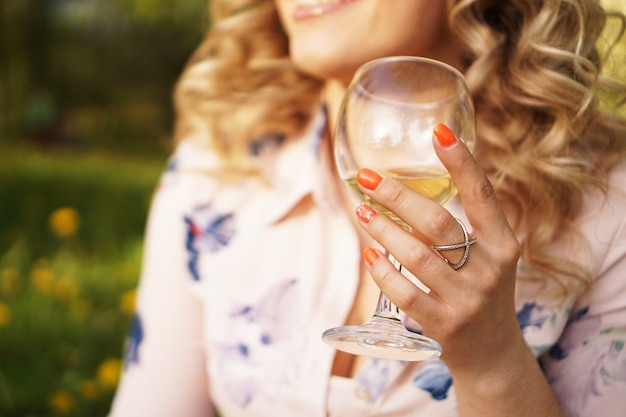 Loira feliz segurando uma taça de vinho branco durante um piquenique ao pôr do sol no parque verde em dia de verão
