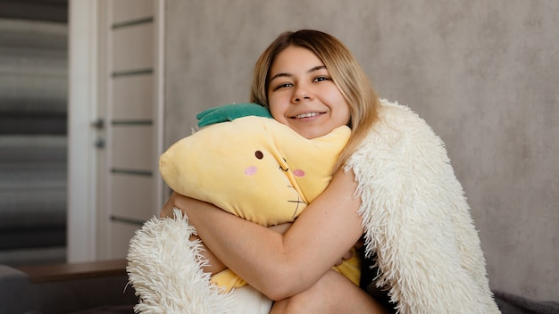 Loira feliz sob um cobertor branco pela manhã abraça um travesseiro amarelo. conceito de manhã feliz