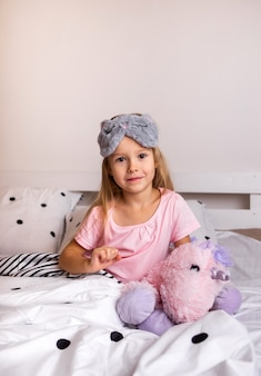 Loira fofa de pijama está sentada na roupa de cama com um brinquedo macio na cama no quarto