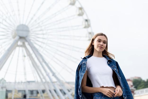 Loira fofa e roda gigante ao ar livre Foto gratuita