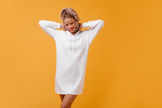 Loira fofa relaxando com um suéter esportivo longo