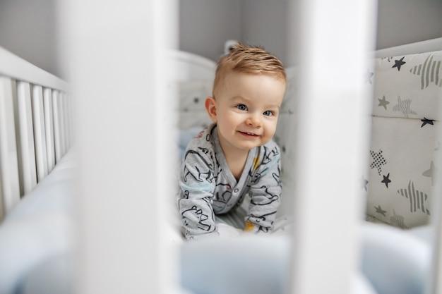 Loira fofa sorridente garotinho deitado de bruços em seu berço e curiosamente olhando algo interessante.