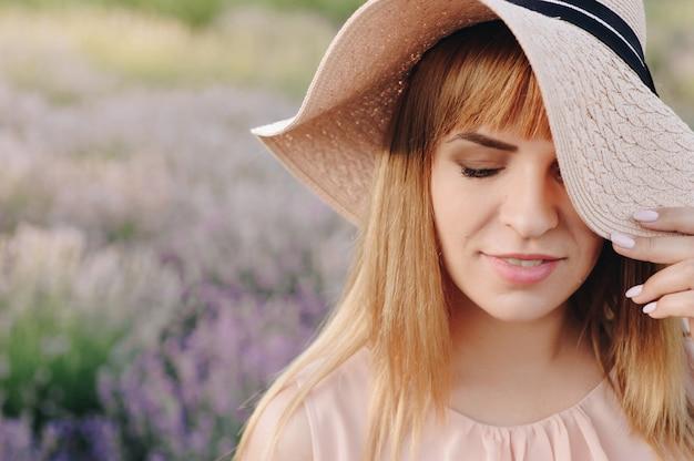 Loira garota em um vestido bege e chapéu de palha. campo de lavanda.