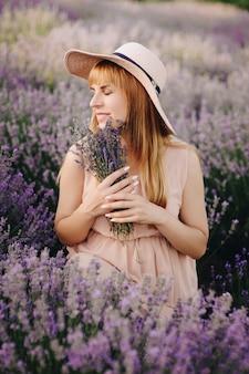 Loira garota grávida em um vestido bege e chapéu de palha. campo de lavanda. em antecipação de uma criança. a idéia de uma sessão de fotos. caminhe ao pôr do sol. futura mãe. retrato. buquê de flores.