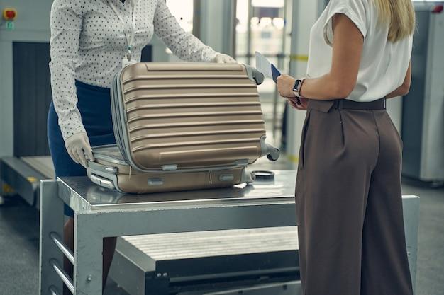 Loira gentil do sexo feminino segurando seu cartão de embarque e olhando para o trabalhador da segurança durante o exame de sua mala