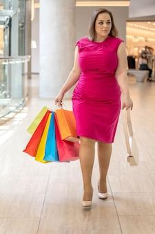 Loira glamourosa e tamanho grande em um vestido rosa sedutor indo com sacola de compras