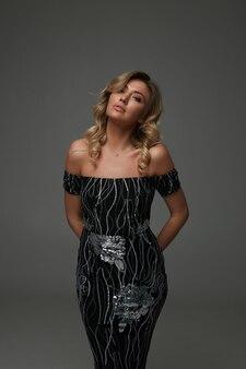 Loira incrível com penteado longo encaracolado e maquiagem natural em estúdio para revista de moda. usando vestido de festa preto com brilhos e sapatos de salto alto. modelo profissional, linda senhora