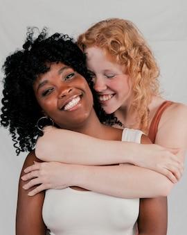 Loira jovem abraçando seu amigo africano contra fundo cinza