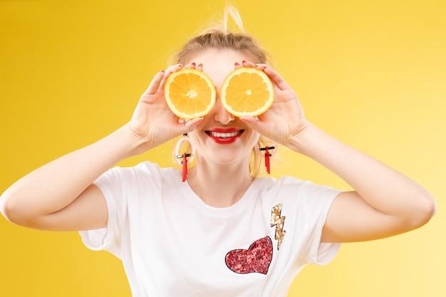 Loira jovem alegre posando com laranjas frescas