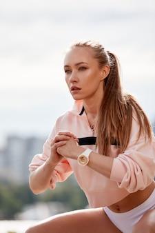 Loira jovem atlética fazendo agachamentos em um parque em um ambiente urbano. mulher atraente atlética, exercício ao ar livre pela manhã, copie o espaço. saúde, conceito de fitness.