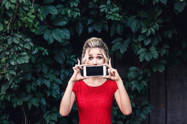 Loira jovem atraente com um vestido vermelho fecha a boca com um smartphone.