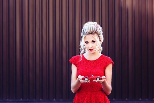Loira jovem atraente em um vestido vermelho segurando um carro de brinquedo. conceito de locação e compra de um carro