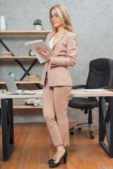 Loira jovem bem vestida empresária de pé em documentos de leitura de mesa no escritório