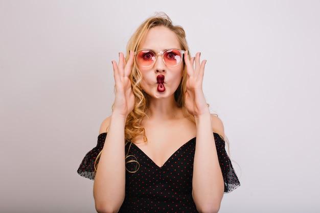 Loira jovem brincalhão com lábios vermelhos fazendo cara de peixe, jovem se divertindo, sendo louca. usando óculos cor-de-rosa elegantes, vestido preto, tem longos cabelos cacheados.