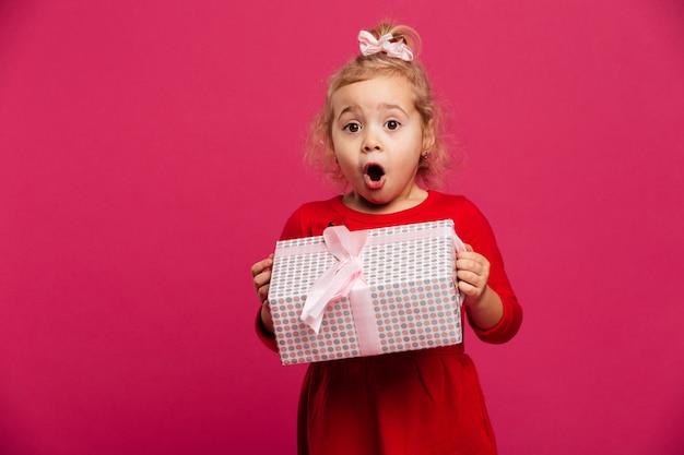 Loira jovem chocada no vestido vermelho, segurando a caixa de presente