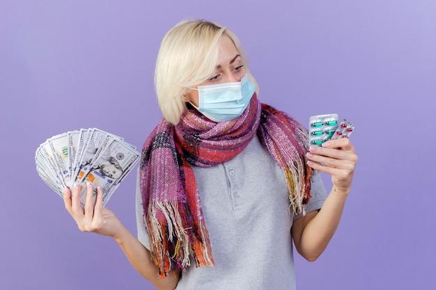 Loira jovem confiante e doente, usando máscara médica e lenço, segura dinheiro e olha para pacotes de comprimidos médicos isolados na parede roxa