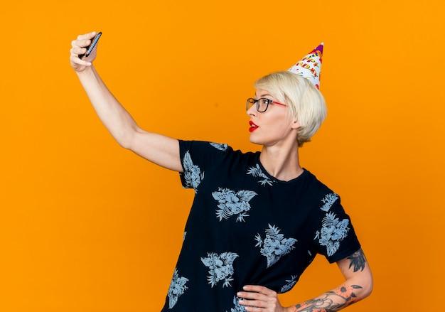 Loira jovem confiante e festeira usando óculos e boné de aniversário, tirando uma selfie e mantendo a mão na cintura isolada em um fundo laranja