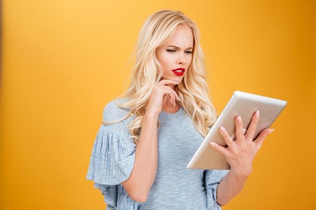 Loira jovem confusa usando computador tablet.