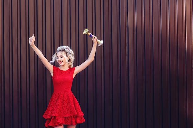 Loira jovem e atraente com um vestido vermelho segura a taça do campeão e está muito feliz.