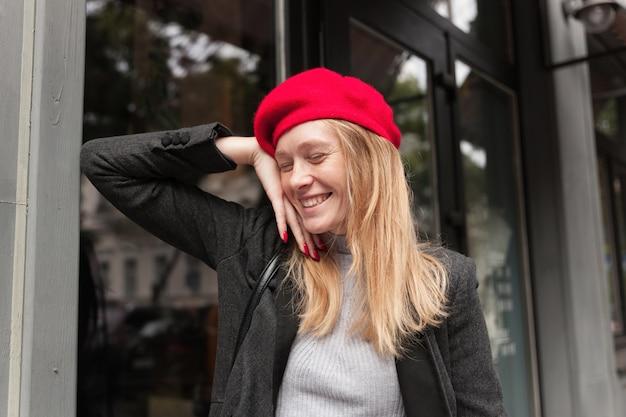 Loira jovem e bonita e feliz com penteado casual, mantendo os olhos fechados enquanto sorri agradavelmente, inclinando-se no parapeito da janela enquanto fica em pé sobre o exterior do café