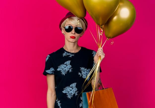 Loira jovem e triste festeira com chapéu de festa e óculos escuros segurando balões e sacos de papel isolados em um fundo carmesim com espaço de cópia
