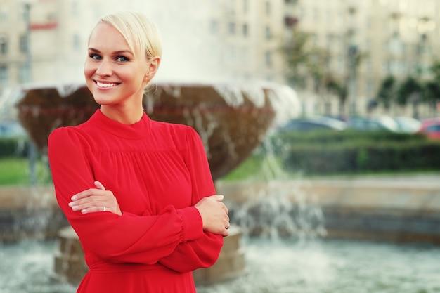 Loira jovem elegante com vestido vermelho, dia de verão