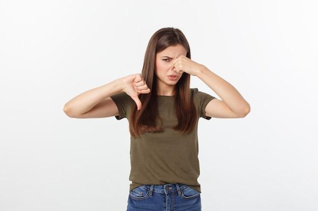 Loira jovem enojada, fechando o nariz com os dedos. isolado sobre o fundo branco