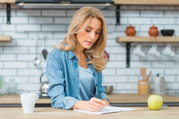 Loira jovem escrevendo com caneta no caderno sobre a mesa de madeira