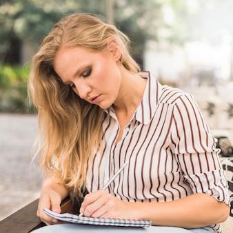 Loira jovem escrevendo no caderno com lápis